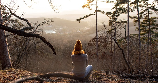 Girl sitting  in forest with beautiful view