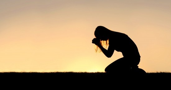 Silhouette of a young Christian woman is bowing her head in prayer, and desperation outside during sunset.