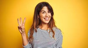 woman holding up three fingers