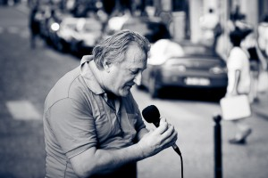 B&W man in street with microphone