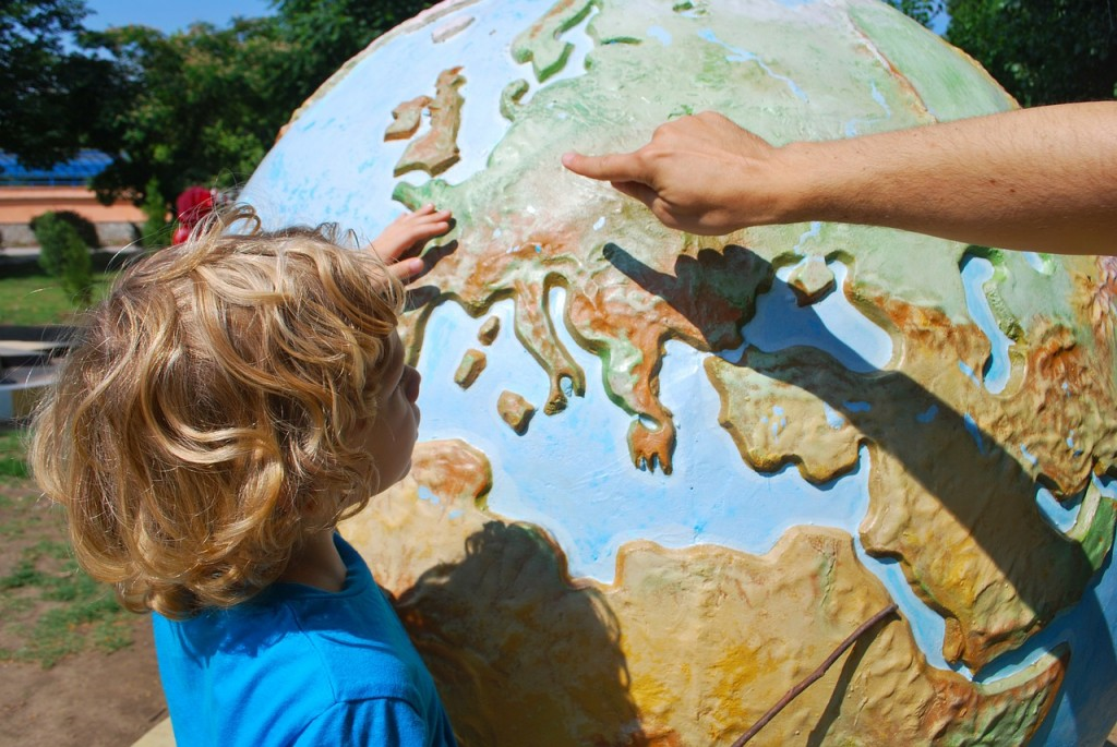 An adult is pointing at a globe to a child