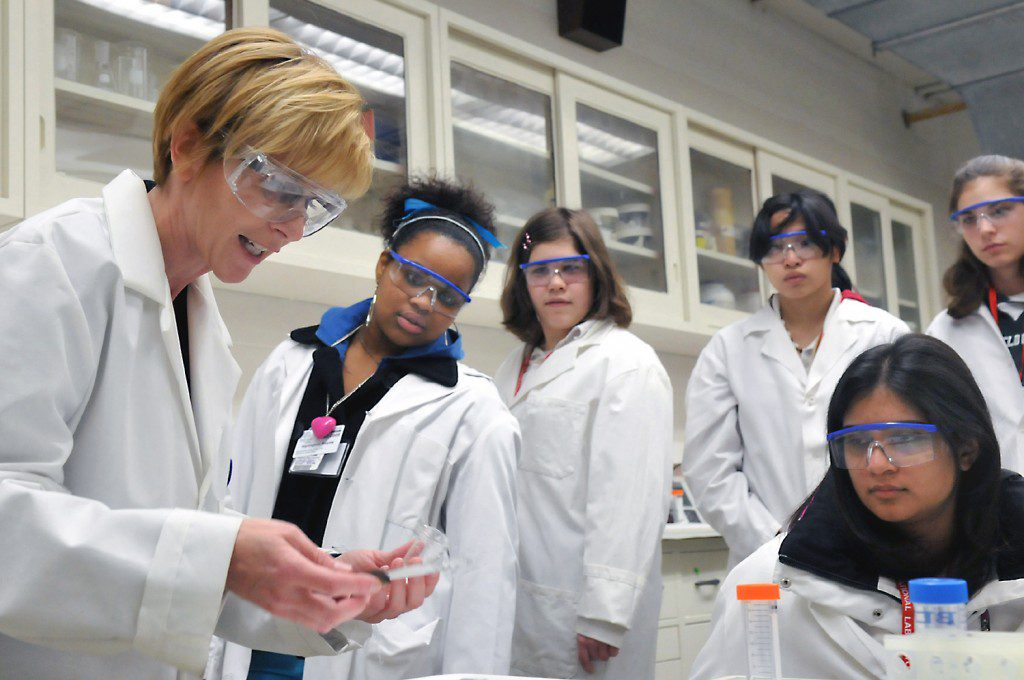Diverse race women in labcoats in a lab environment.