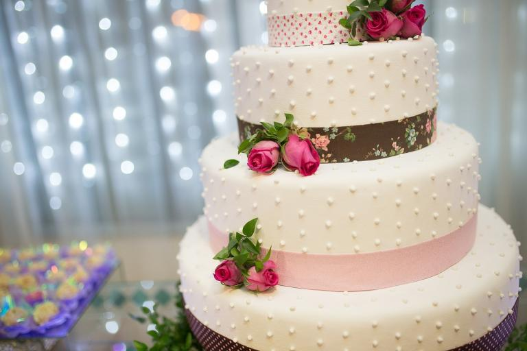 A white wedding cake with brown and pink trim around each layer.