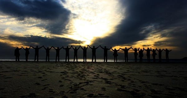 People standing in solidarity on a beach (image via Pixabay)