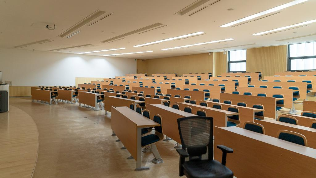 Image of an empty lecture hall filled with chairs and desks.