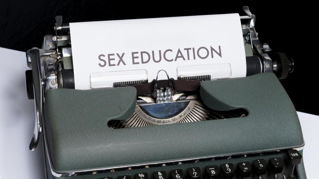 type writer with a piece of paper inserted, on which is printed, sex education