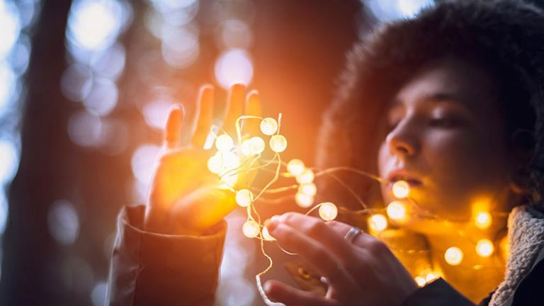Woman looking at and touching golden fairy lights