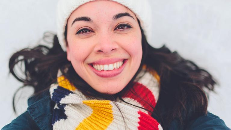 smiling woman in winter hat and scarf