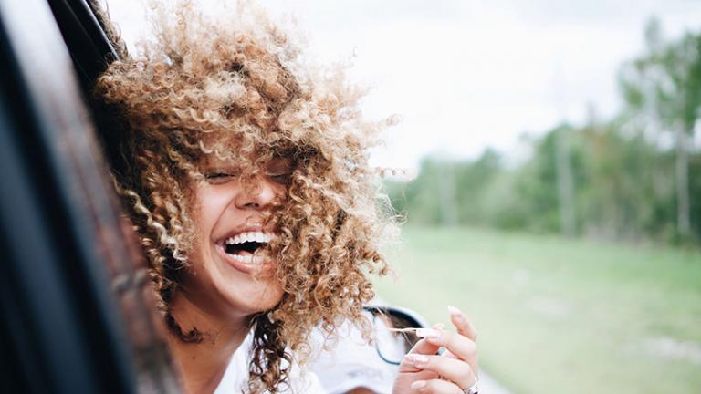 woman with curly hair sticking her head out of a moving car