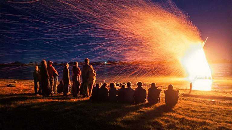 Group of people watching a blazing bonfire.