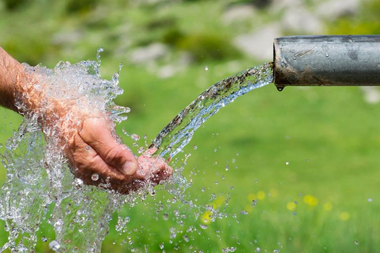 hand under running water through outdoor spout
