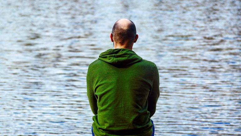 man staring at a lake