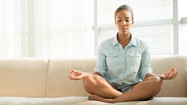 woman meditating on a couch