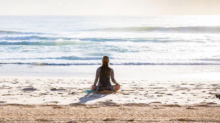 woman meditating in the ocean waves