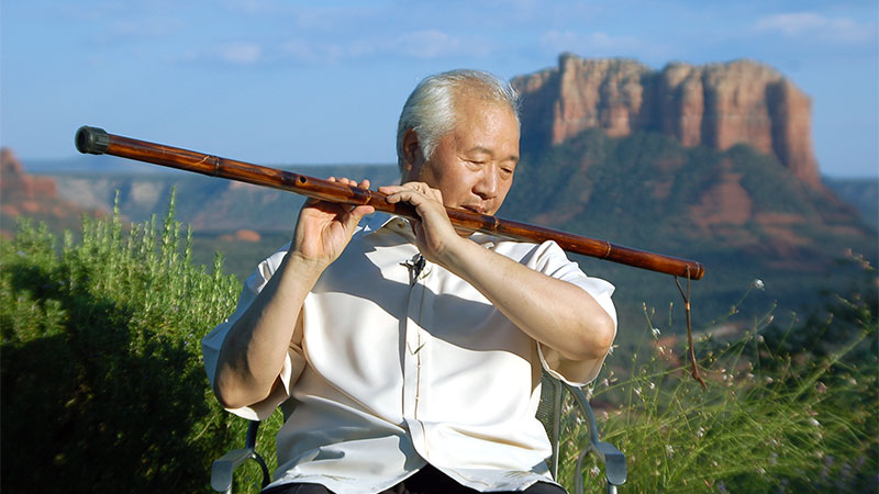 Ilchi Lee playing a staff flute