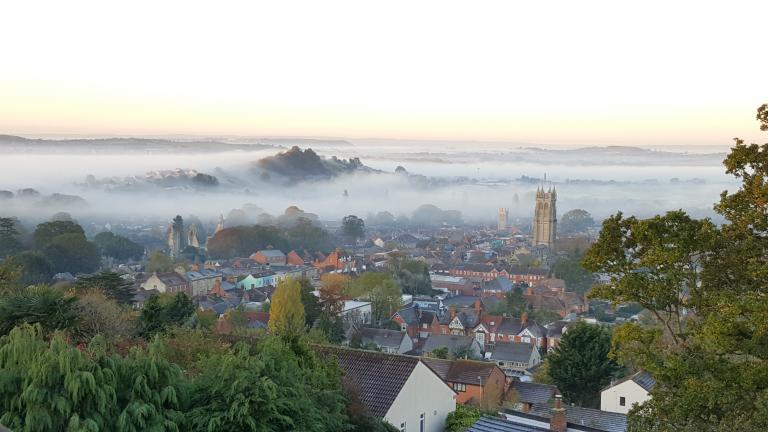 The Somerset Town of Glastonbury, with St. John's Church, the Abbey and Wearyall Hill - in the morning mist of Autumn. Photo by Sorita d'Este, 2018