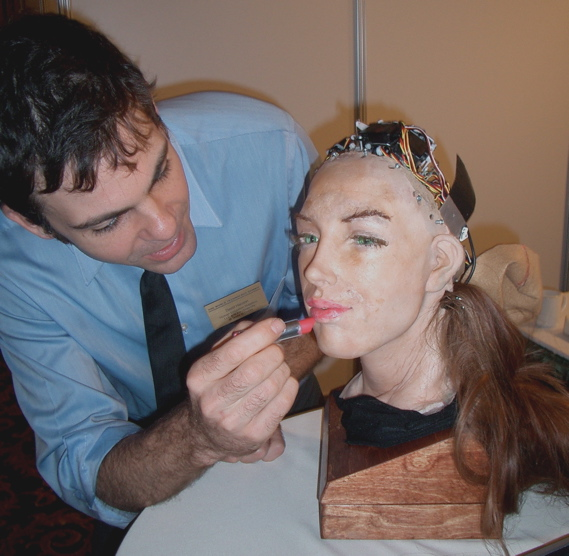 Description A robot by Human Emulation Robotics. Lipstick is carefully applied by the designer -- easier when the power is off. She frowns and shakes her head if you get too close. Date8 October 2004, 11:46:20 SourceFlickr AuthorSteve Jurvetson from Menlo Park, USA ReviewerGreudin (CC BY 2.0)