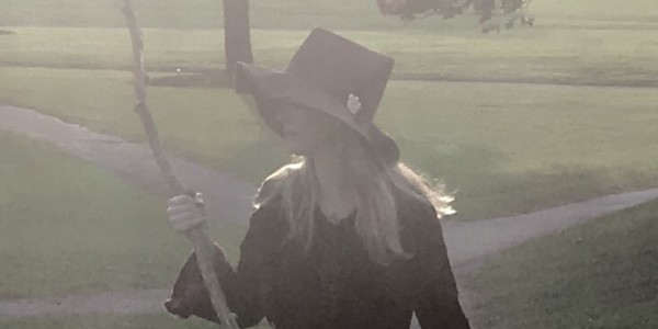 Woman with pointy hat and staff of witchcraft, looks back over the path she's walked.