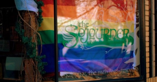 Front Window of The Sojourner Whole Earth Provisions with our Pride Flag