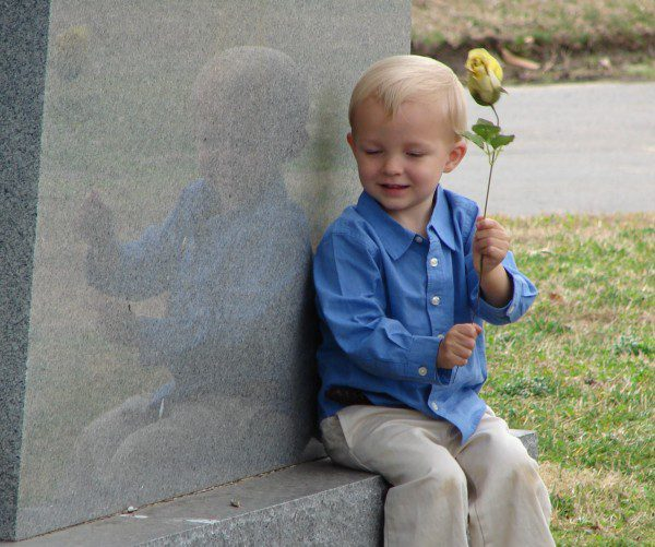 boy holds rose and sits on a gravestone.