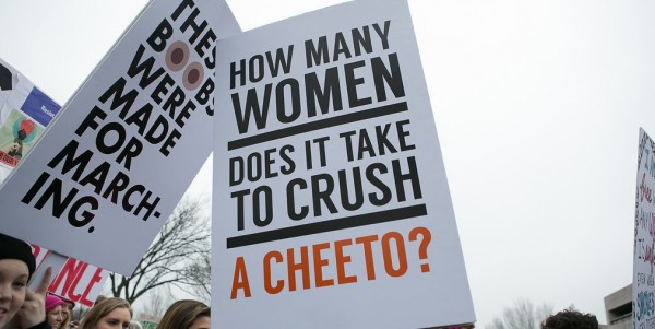 Sign reads: How many women does it take to crush a cheeto?