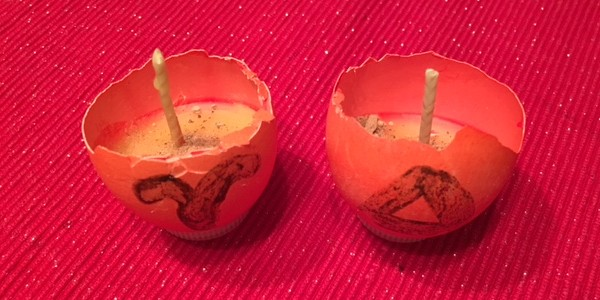 half an eggshell dyed red, filled with a beeswax candle, with herbs and stone chip
