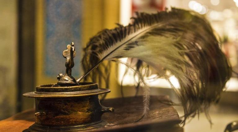 Feather Quill in brass ink pot on antique desk