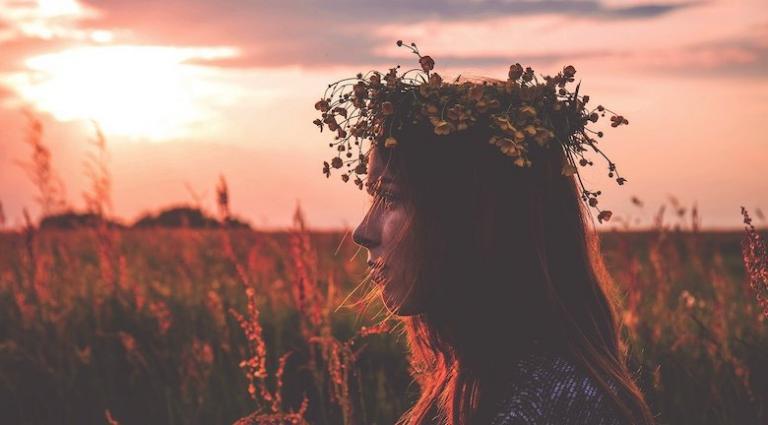 Woman wearing flower crown in sunset