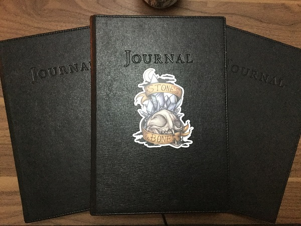 Three of my black books where I record my most important lore. Photo by Coby Michael. Art sicker by Zaheroux.