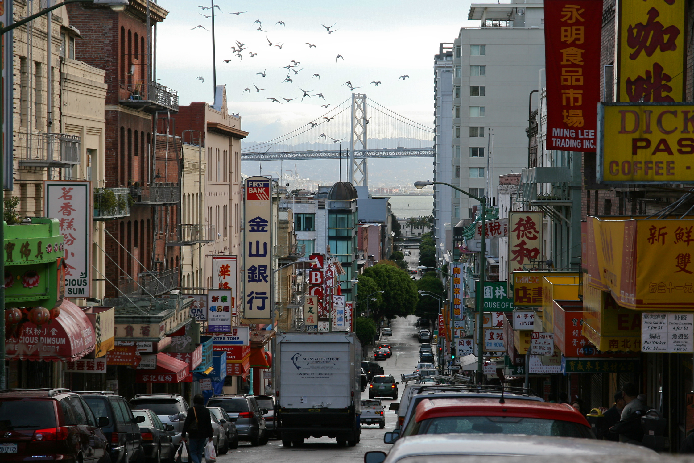 Chinatown in San Francisco, CA. In the background you can see the Bay Bridge. - by Christian Mehlführer, 27 November 2006 (San_Francisco_China_Town_MC.jpg) (CC BY 3.0 [https://creativecommons.org/licenses/by/3.0/deed.en]), via Wikimedia Commons