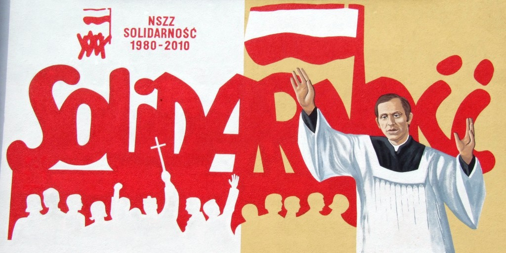30-years of Solidarity (Polish trade union) mural in Ostrowiec Swietokrzyski (priest Jerzy Popiełuszko in foreground) - by Krugerr (Ostrowiec_Solidarnosc_20100815 (1).jpg) [CC BY-SA 4.0 (https://creativecommons.org/licenses/by-sa/4.0/)], via Wikimedia Commons