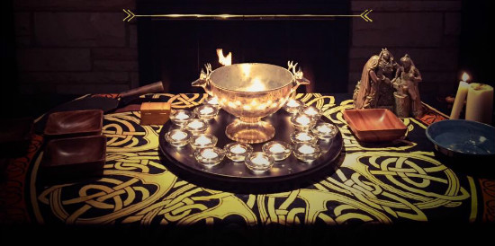 An altar with a silver bowl surrounded by lit candles.