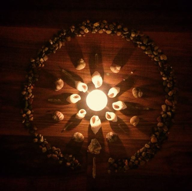 a central candle lights up a circular pattern of shells and stones creating a natural mandala.