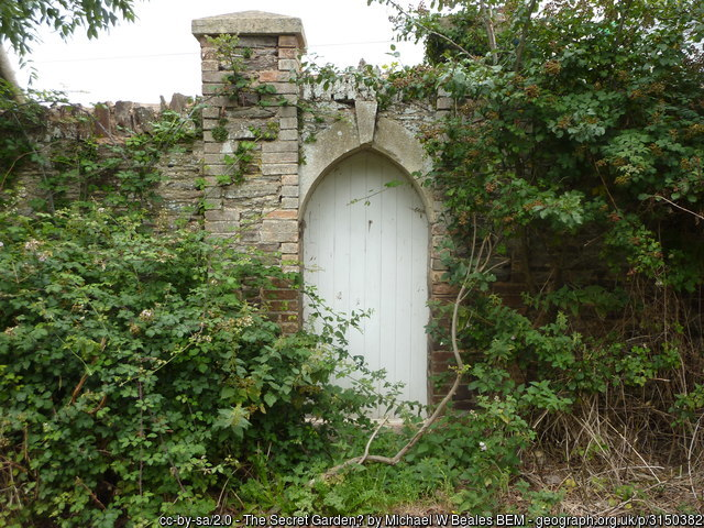 An image of a white wooden door in a grey stone wall surrounded by greenery.