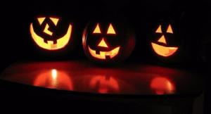 Three Jack-O-Lanterns glowing in the dark.