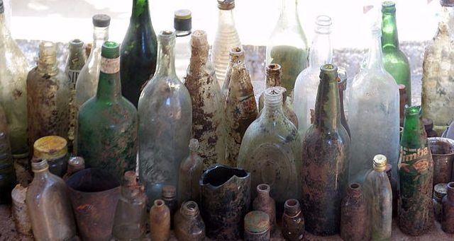 Old glass bottles of all shapes and sizes with mud and residue caked on the inside and outside.