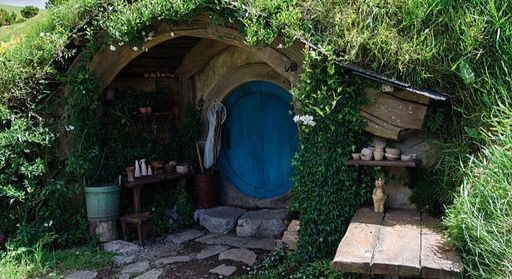 A hobbit hole with a round blue door, some pottery on a niche grass above the door and a flagstone path leading up to it.