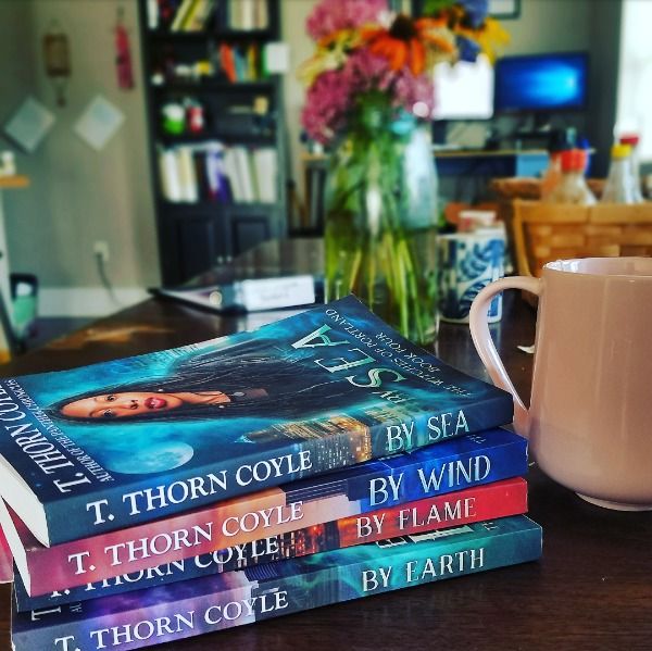 A view of my little abode including new coffee mug, flowers and a stack of Coyle's books.