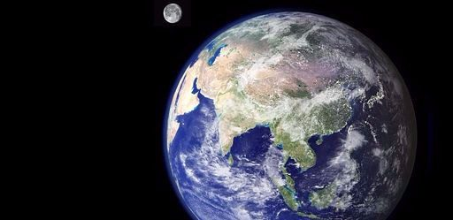 The earth set in the backdrop of the vast blackness of space with the moon a small circle next to Her.