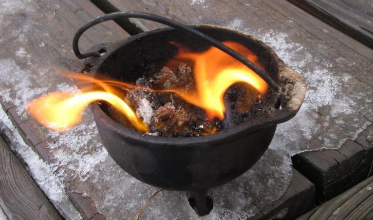 a small cauldron with a fire sitting on a deck with the last bits of ice and snow covering the wood.