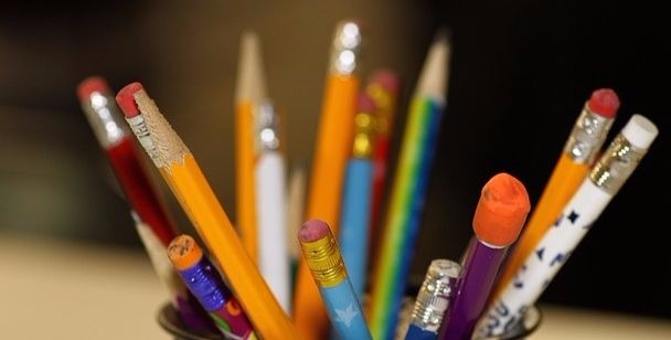 A selection of kids pencils swirling out of a mug. They show wear and eraser use. These are working pencils.