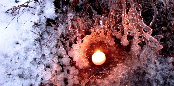 Surrounded by snow a single candle reflects red light on the ice covered branches.