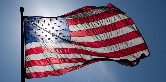 A United States flag blowing in the wind backlit by the sun in a blue sky.