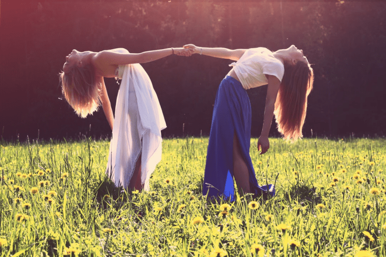 Two women holding hands and leaning away so that it is only their held hands that keep them upright. They are standing in a sunny bright field.