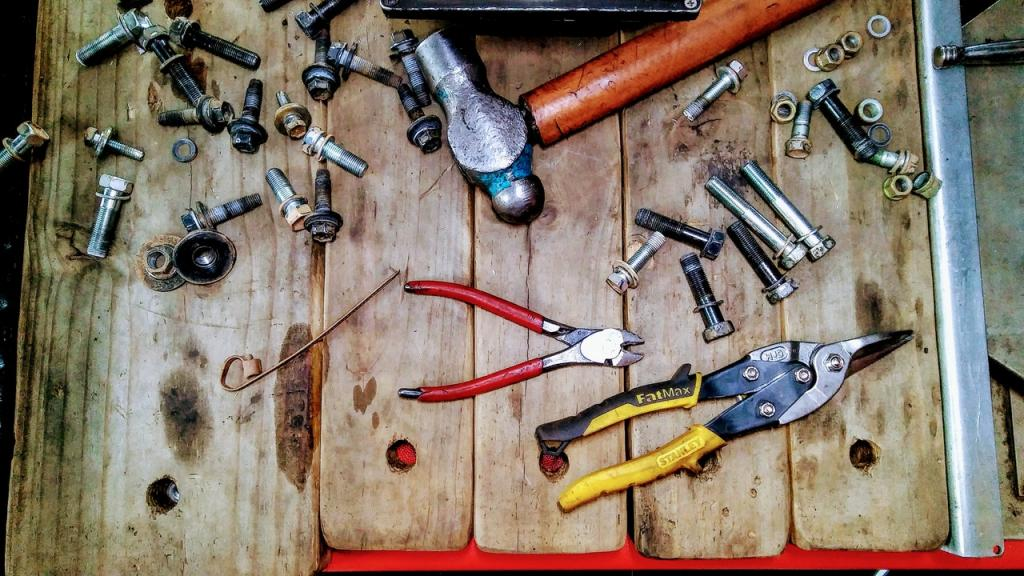 An array of tools and bolts used in repair set on an old wooden bench.