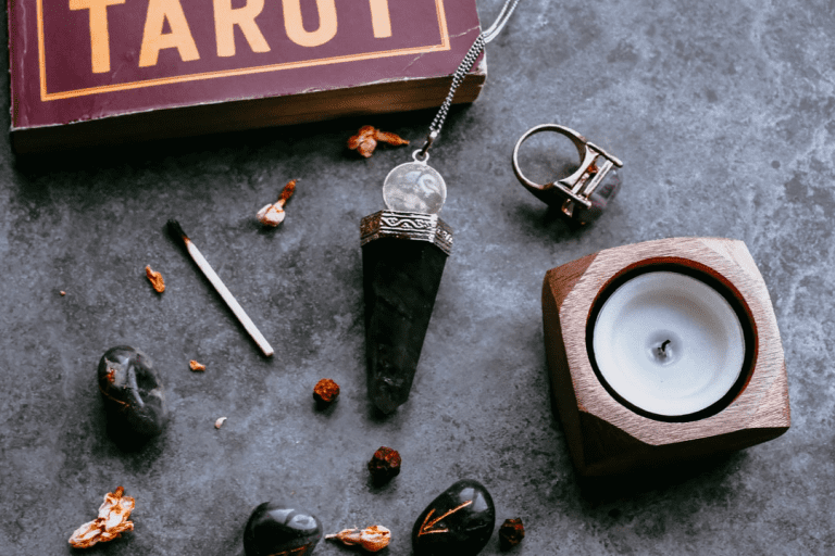 A photo of various accoutrements of ritual: a tarot book, pendulum, burnt out match and candle, runes, and an amethyst ring.