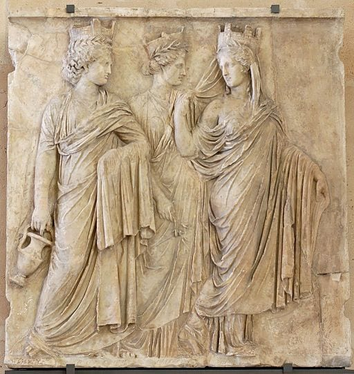 A pale stone bas relief of three goddesses in finely detailed robes with crowns. One carries a pitcher.