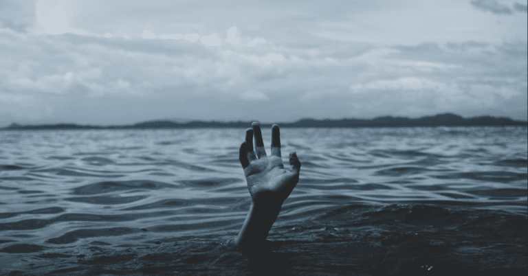 A hand reaches up from the watery depths out of the grey light.