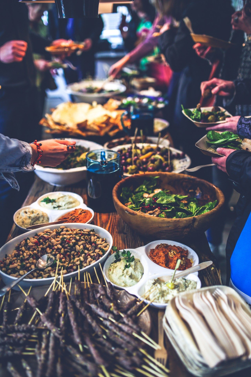 A long buffet style table filled with food where people are reaching in to share and eat.