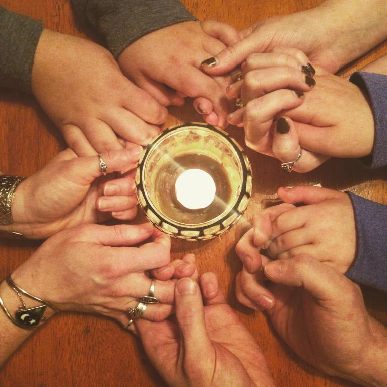 Hands being held in a circle around a lit candle.